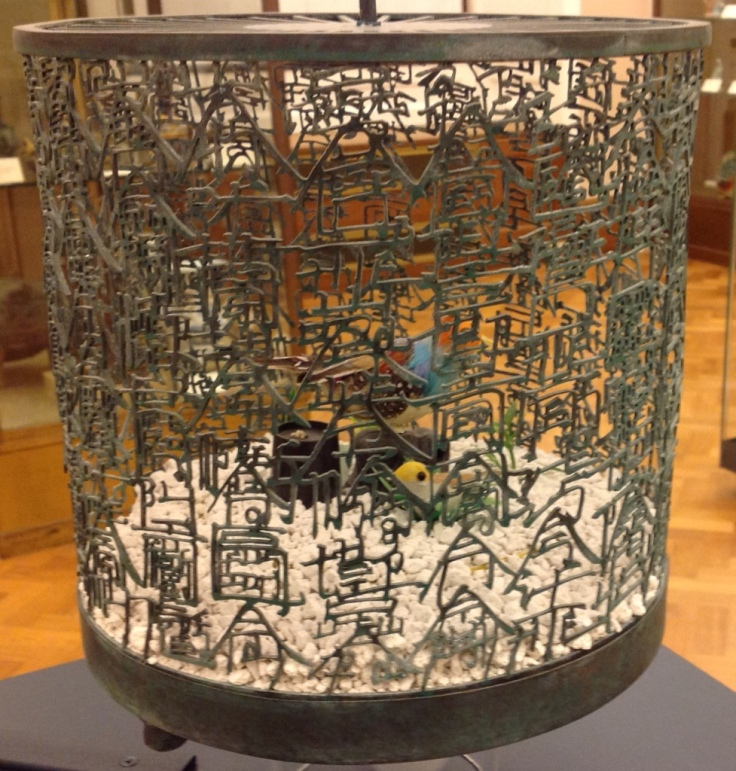 """Xu Bing, Bird Language, 2003 Four brass and copper birdcages containing sound-activated toy birds, the cage mesh composed of English and """"square word calligraphy"""", gravel."""